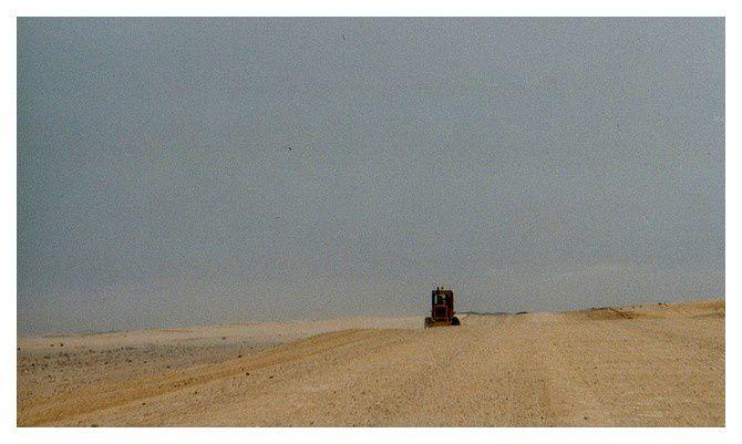 un engin de travaux aplanissant la piste très large