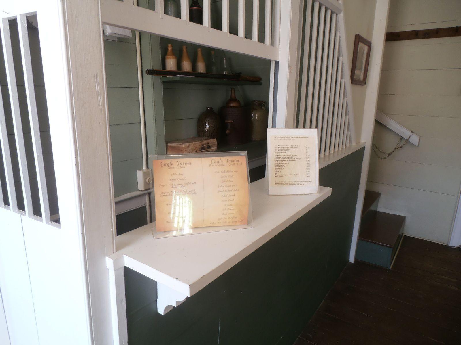 Au rez-de-chaussée, on a pris parti de la montée d'escalier pour installer le bar. Le serveur devait être un peu à l'étroit... En tout premier plan, le visiteur peut consulter les tarifs de l'époque.