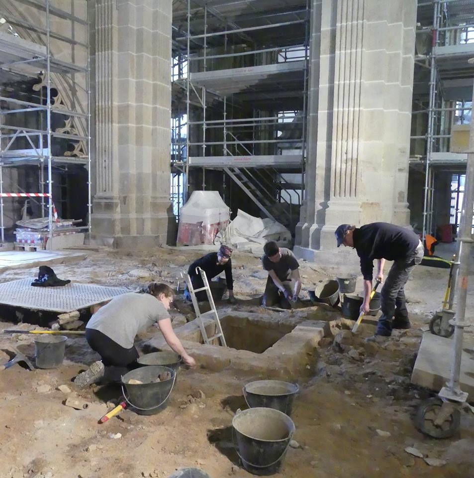 Les archéologues s'activent devant l'entrée d'une structure souterraine.