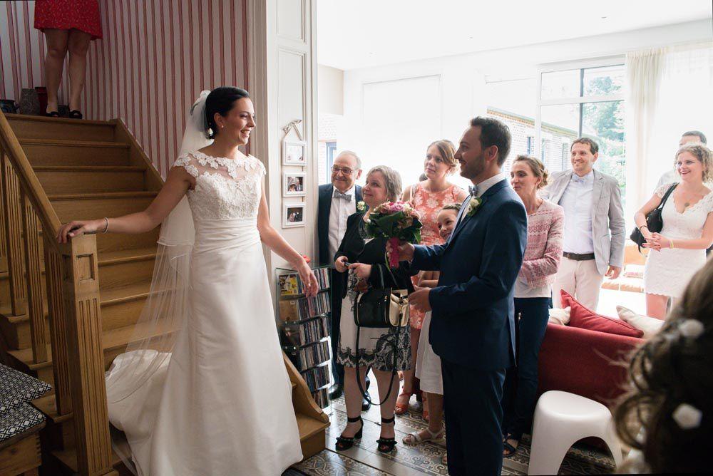 Le marié découvre sa future femme en bas des escaliers et lui remet le bouquet.