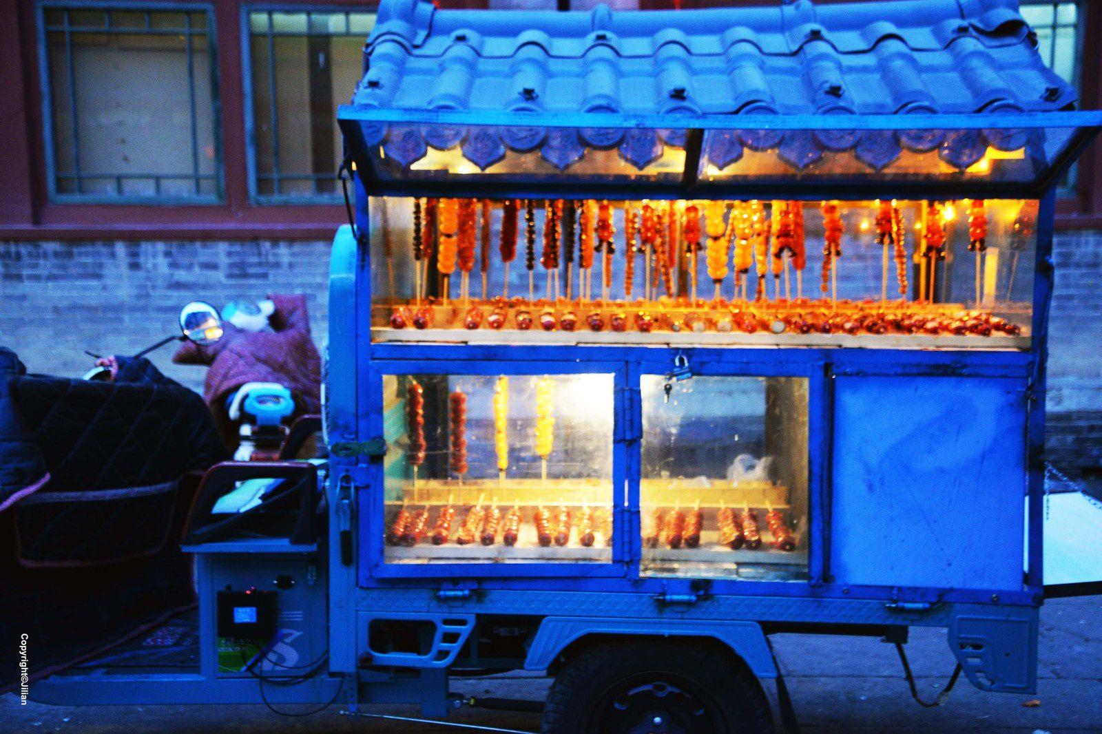 """Carriole de """"tanghulu"""" - 糖葫芦. Brochettes de fruits caraméliés. Les tanghulu traditionnels sont faits avec des azeroles, petites pommes sauvages. Mais, avec la mondialisation, celles aux fraises et aux mandarines font maintenant fureur."""