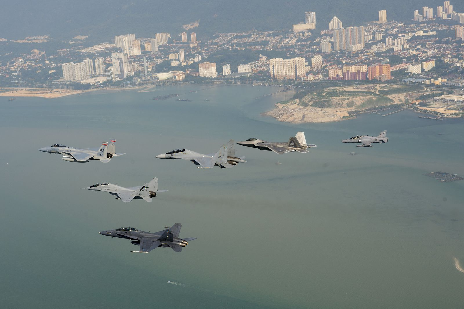 © USAF - Pendant l'exercice COPE TAUFAN 2014, formation d'un F-15C Eagle et F-22 Raptor de l'US Air Force, accompagnés par un F/A-18D Hornet, MIG-29N Fulcrum, Hawk 208 et un Su-30MKM de la Force Aérienne Royale Malaysienne.