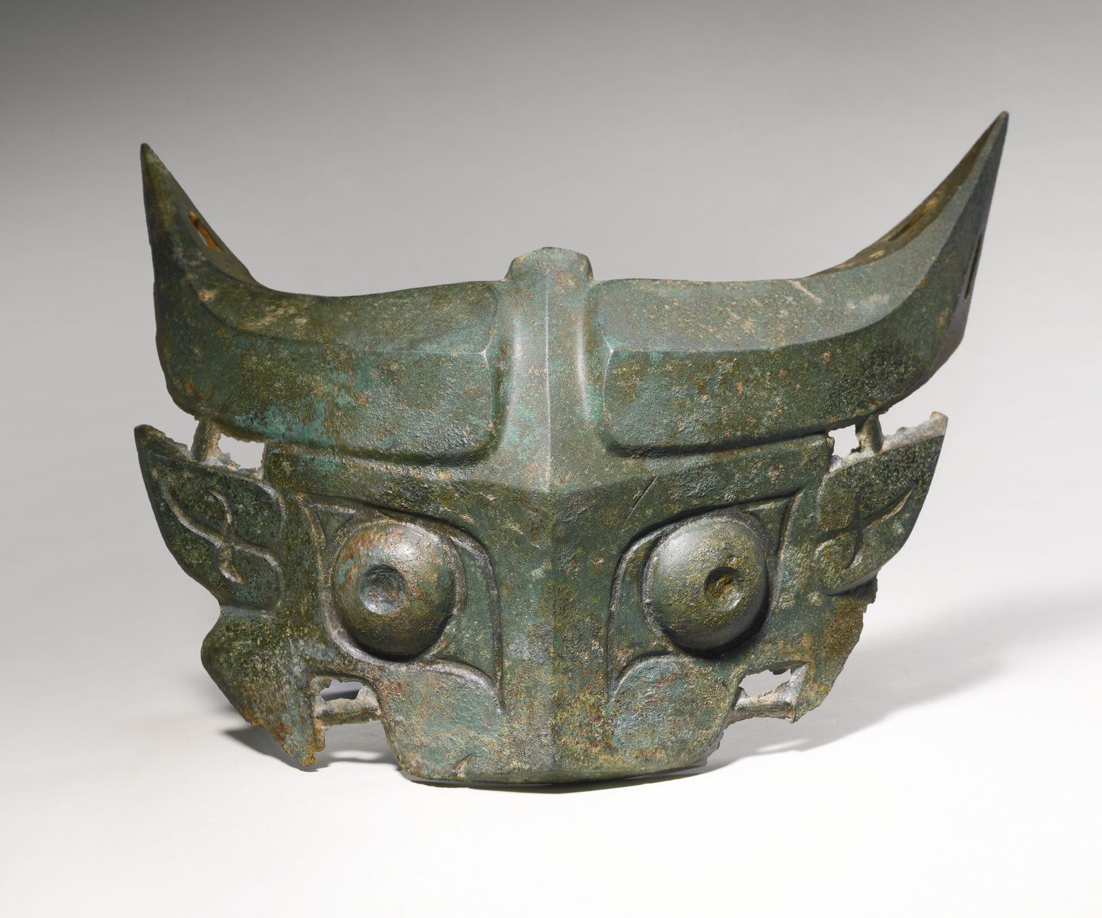 Le taotie chinois est le symbole de l'union -et non l'antagonisme- de l'homme et des forces spirituelles et physiques de la Nature. A BRONZE TAOTIE MASK EARLY WESTERN ZHOU DYNASTY, 11TH-10TH CENTURY BC cast with bulging eyes, flanked by pointed leaf-shaped ears, beneath upcurved bovine horns with hollow tips, the wide upper jaw defined by an out-curved snout and a pair of hooked fangs, with dark green surface patina and widely scattered reddish cuprite encrustation Width 9 in., 22.9 cm. Sothebys http://www.sothebys.com/en/auctions/ecatalogue/2013/magnificent-ritual-bronzes-n09026/lot.10.html