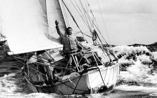 """Robin Knox-Johnston 'né en 1939) est le premier marin connu à avoir fait le tour du monde à la voile sans escale, en 1968-69. """"Le 22 novembre 2014, Robin Knox-Johnston, alors âgé de 75 ans, termine la course transatlantique en solitaire de la Route du Rhum-Destination Guadeloupe à la troisième place dans la catégorie Rhum. Il franchit la ligne d'arrivée sur son Open 60 Grey Power à Pointe-à-Pitre à 16h52 heure locale (20h52 GMT), après 20 jours 7 heures 52 minutes et 22 secondes en mer."""" (Wikipedia)"""