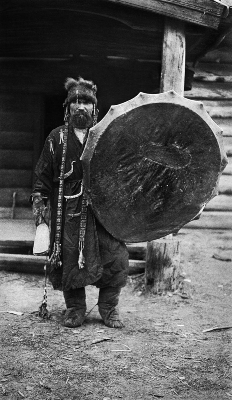 """Shaman  de Tym et son tambour magique.  Son costume est décoré avec des images métalliques de divinités et d'animaux. Photographie: Kai Donner in: """"Parmi les Samoyèdes en Sibérie""""."""