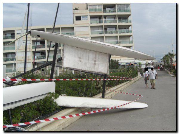 Catamaran couché sur le flotteur babord et occupant partiellement la voie publique qui borde l'enceinte où il était entreposé
