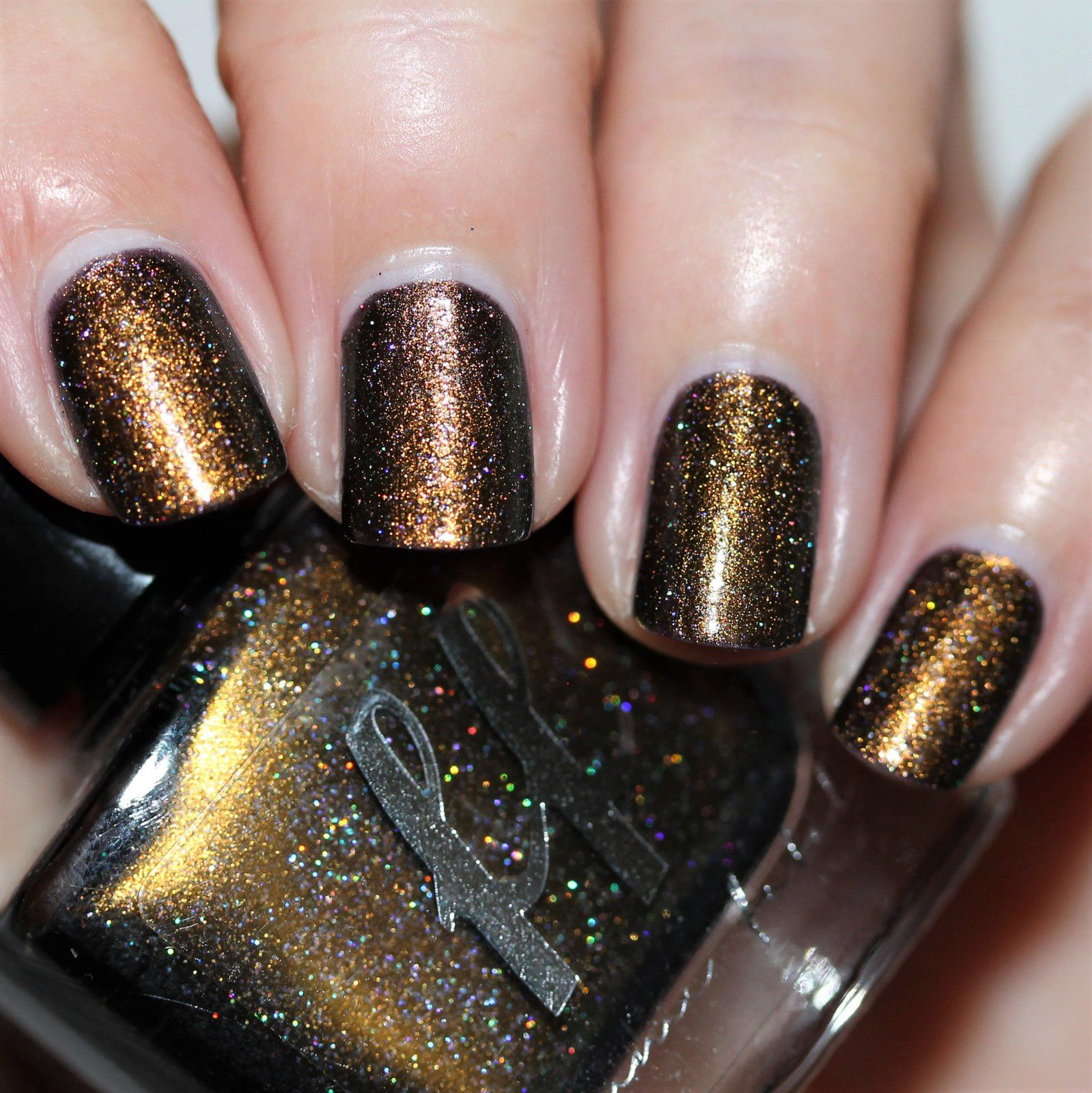 The Two Sphinx (2 coats no top coat), a dark purple base dominated by an olive gold to blue multichrome, and scattered holographic flecks and flakes.