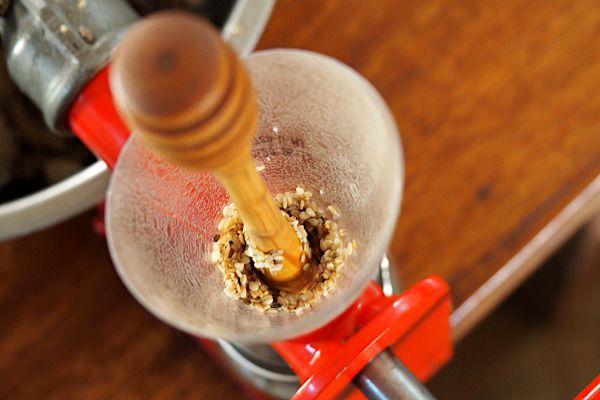 Au bout d'un petit moment, les graines commencent à s'enduire d'huile jusque dans l'entonnoir, ce qui gène la descente des graines. J'appuie alors un peu plus avec mon pilon.