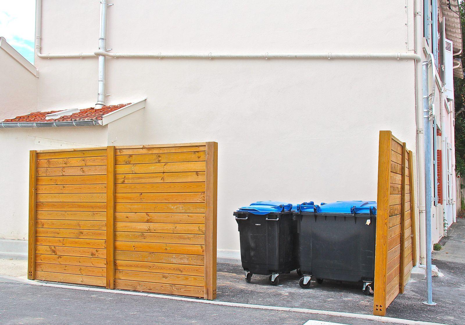 Actuellement sans porte, le dépôt d'enlèvement des déchets laisse apercevoir les bacs à déchets.