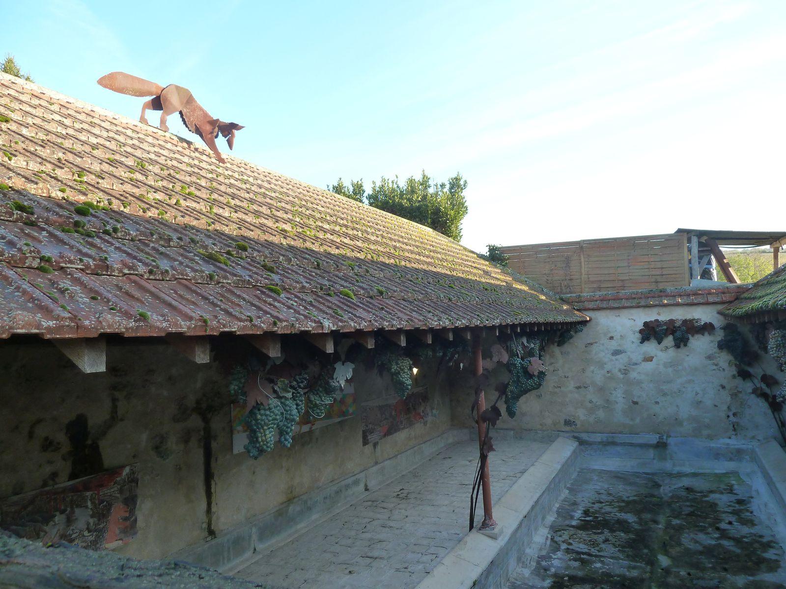 Le renard, sur le toit et les raisins suspendus.