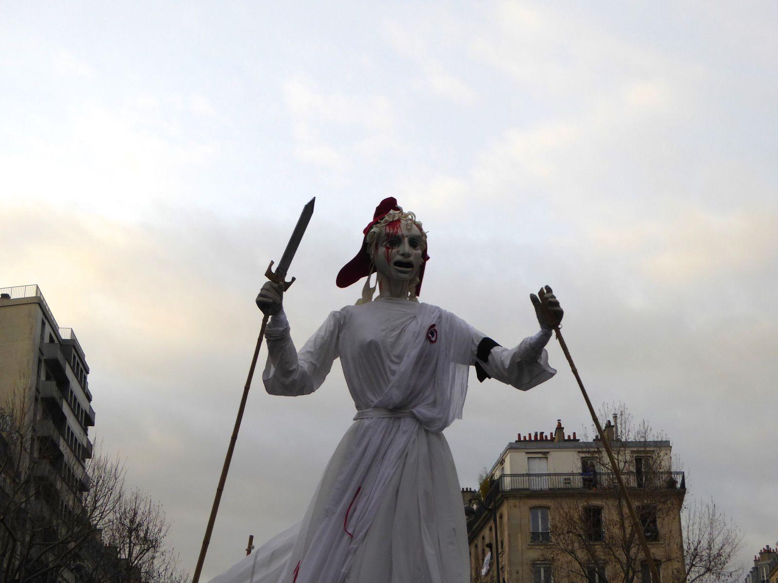 Marianne géante dont le visage est ensanglanté et la colonne de Juillet à la tombée de la nuit.