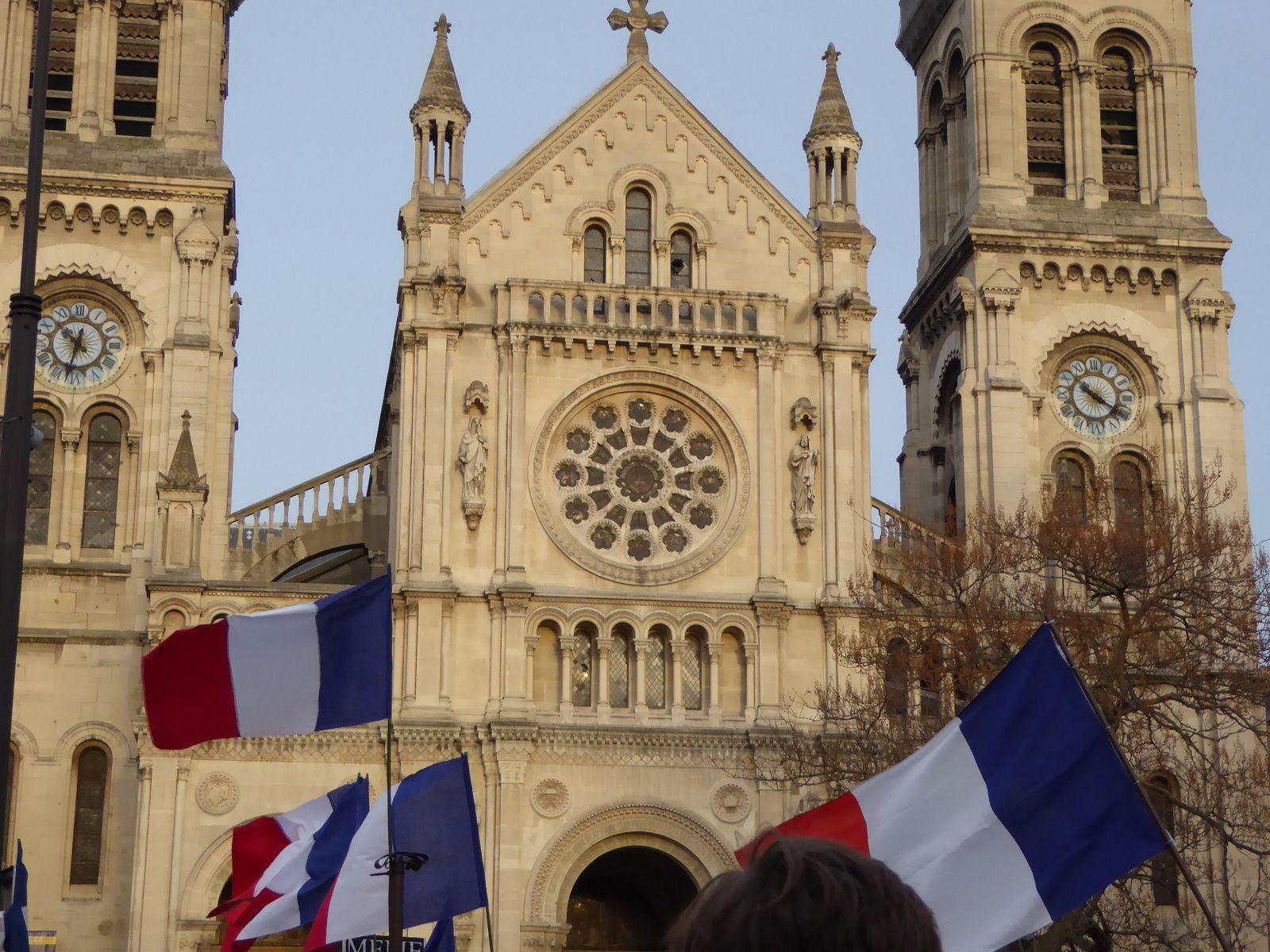 Place Voltaire, devant Saint-Ambroise, la une de Marianne et les drapeaux devant l'église...