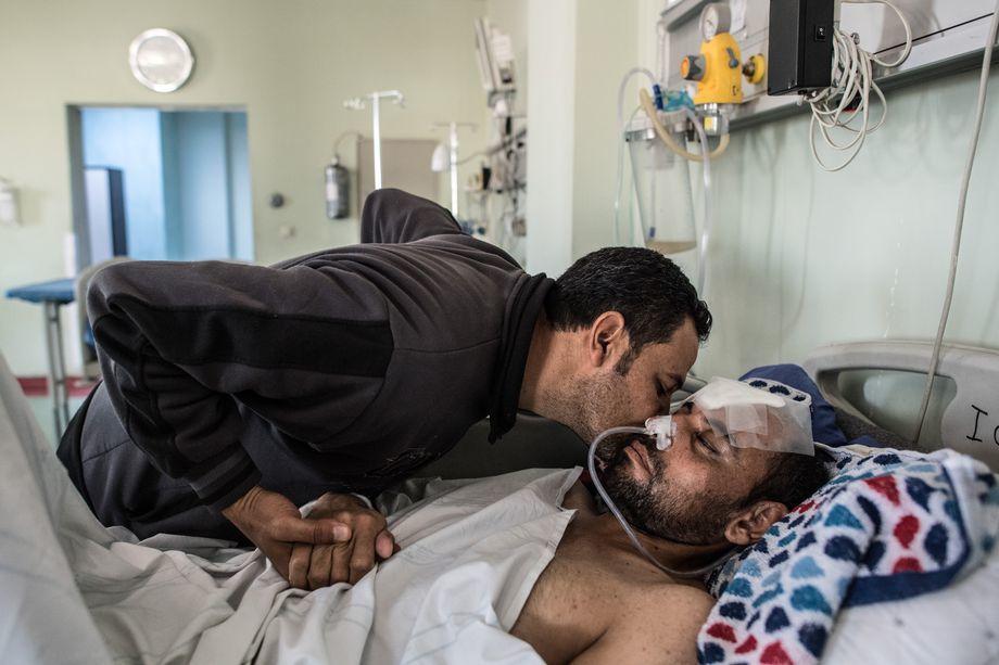 Mohammed Mahmoud, qui a été grièvement blessé à la tête par des éclats d'obus lors d'une attaque aérienne à Mossoul, est réconforté par son frère Amar Mahmoud alors qu'il repose dans son lit le 17 avril 2017, à l'hôpital d'urgence d'Erbil, à Erbil, en Irak.  Carl Court/Getty Images