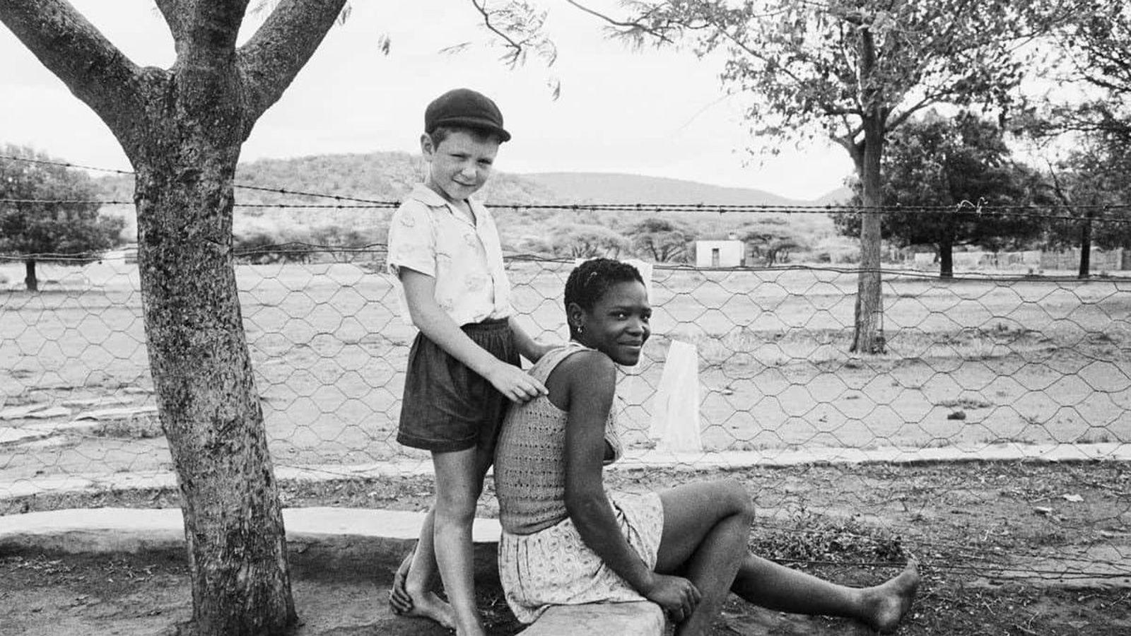 """""""Le fils du fermier avec sa bonne d'enfants, ferme de Heimweeberg, environs de Nietverdiend, Marico Bushveld, province du Nord Ouest"""", 1964 de David GOLDBLATT - Courtesy David Goldbatt et Goodman Gallery Johannesburg et Cape Town."""