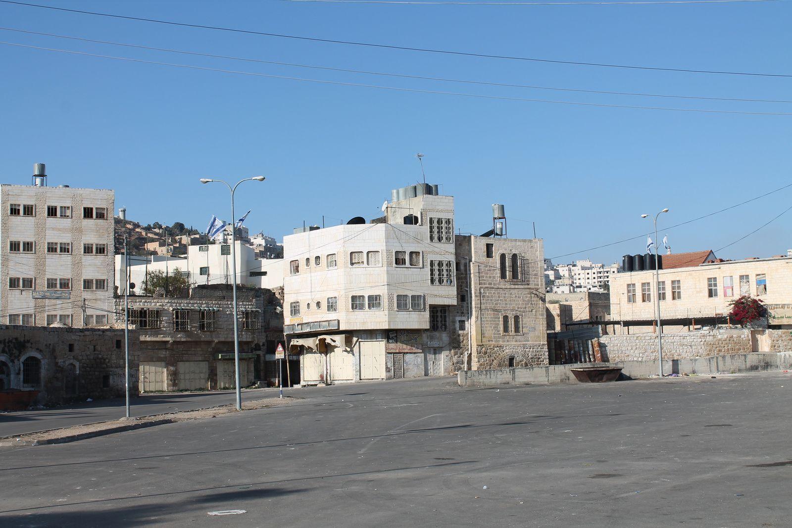 Cette place à l'entrée d'Hébron fut la place du marché. C'était un centre important d'animation pour les Hébronites. Suite à la 2e Intifada, les autorités militaires israéliennes y ont interdit toute activité. C'était un lieu vivant qui a été anesthésié.