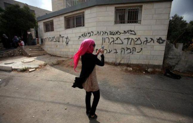 """Une jeune Palestinienne regarde les graffitis  en hébreu laissés par les colons israéliens. Il est écrit : """"Mort aux Arabes""""..."""