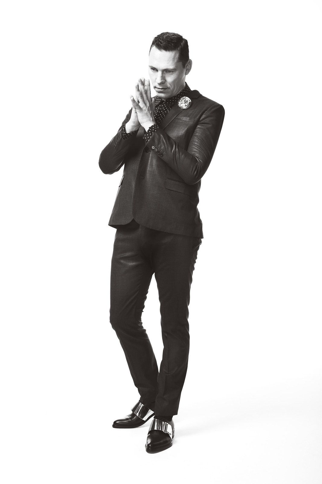 Tiësto wears a suit and shirt by Saint Laurent, pin by Chanel and shoes by Givenchy.