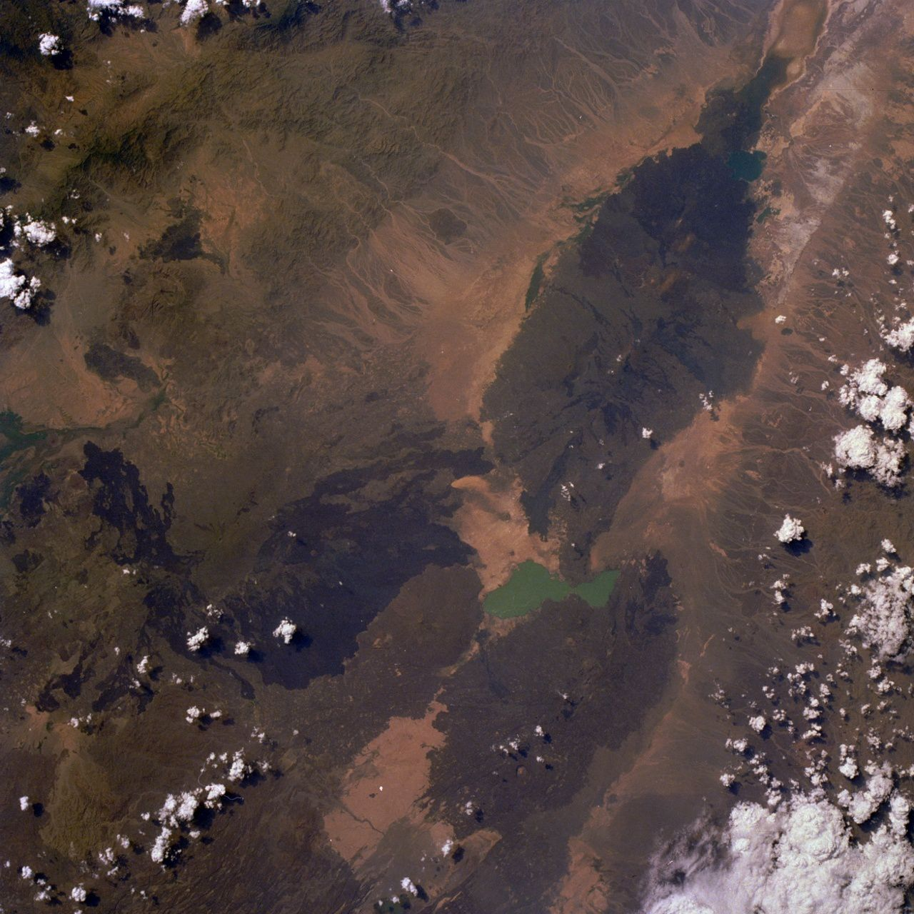 "Le massif de l'Erta Ale - photo NASA  STS026-033-080 / 30.09.1988 - 11h35 GMT (Erta Alle, a shield volcano located within the Rift Valley of northern Ethiopia, is visible in this near-vertical photograph taken north of turquoise Afrera Ye Ch'ew Lake. The volcano, called ""the smoking mountain"" by the local tribesmen, has an active lava lake (barely discernible in the photograph) approximately 150 feet (46 meters) wide, which has been in a constant state of eruption since the late 1960s.)"