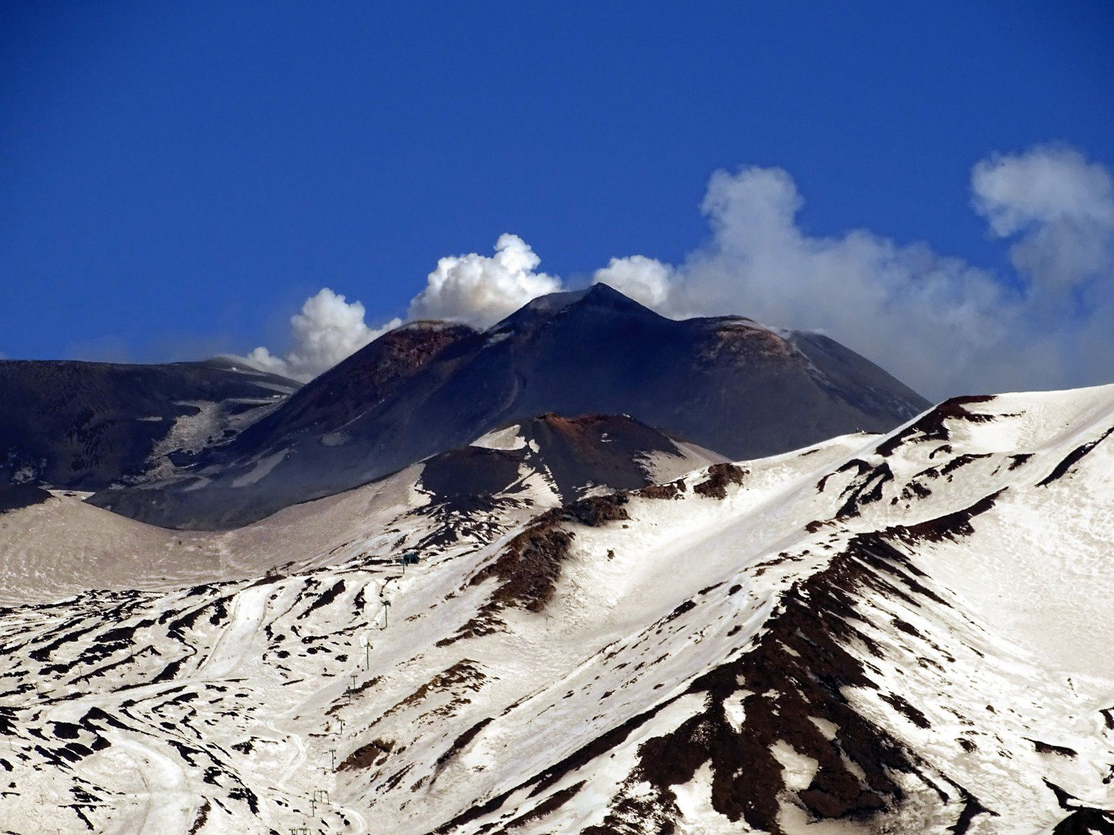 As Boris Behncke says, Etna has a new baby, seen here from Nicolosi on March 2, between the SEC on the left and the NSEC on the right. In the foreground you can see the pillars of the cable car. - photo Boris Behncke 02.03.2017