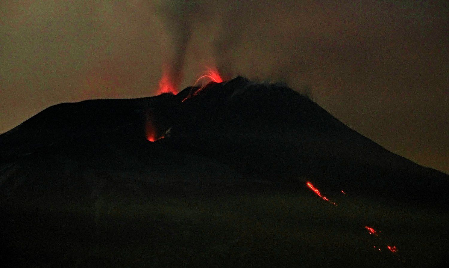 Etna - in the evening of 20.03.2017 - strombolian activity in the SEC (center), incandescence at the Voragine (on the left), and lava flow in the Valle del Bove - photo Boris Behncke