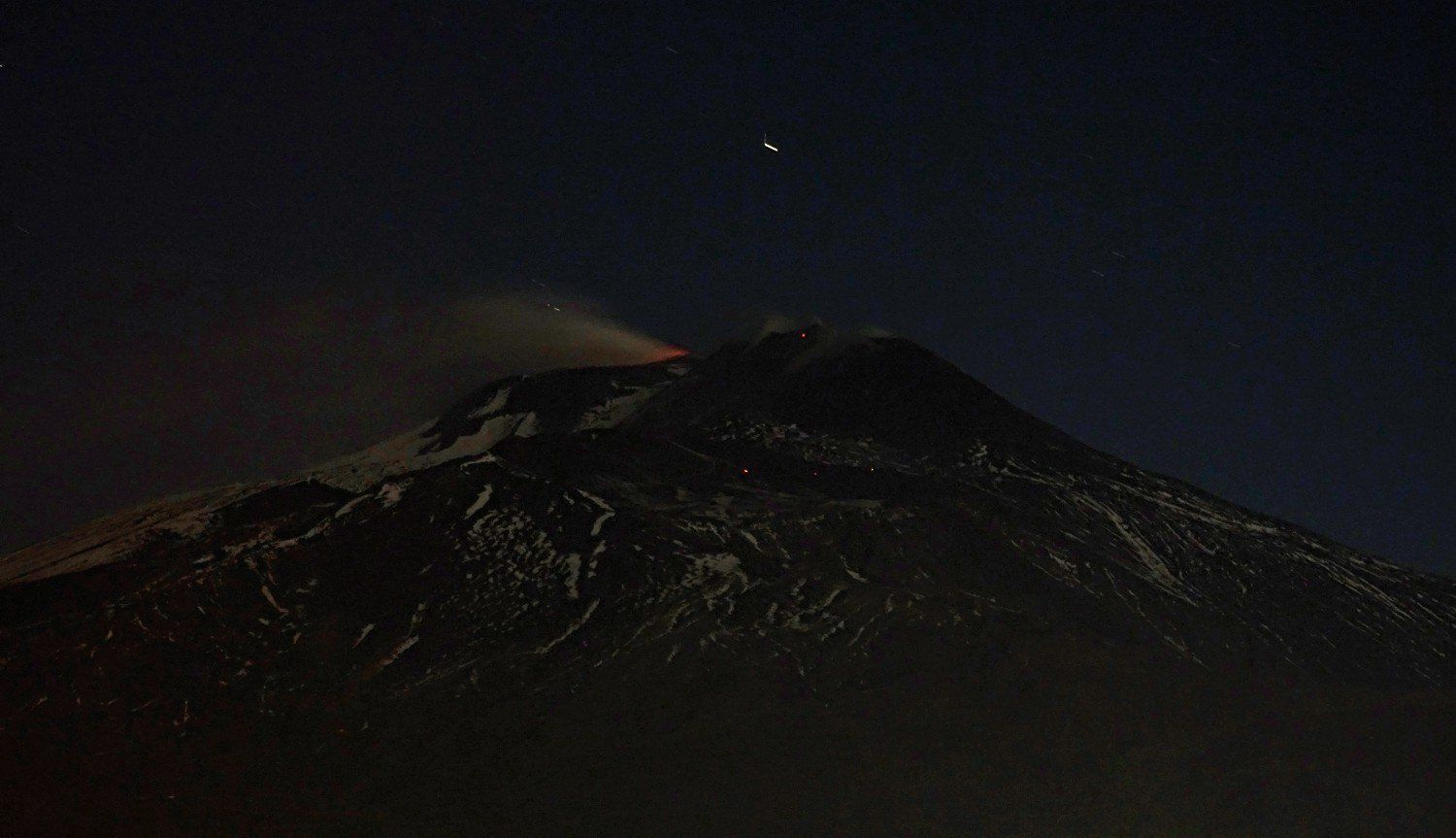 Etna 11.04.2017 - Only a weak incandescence at the Voragine and some glow on the lava flow illustrate the night activity - photo Boris Behncke