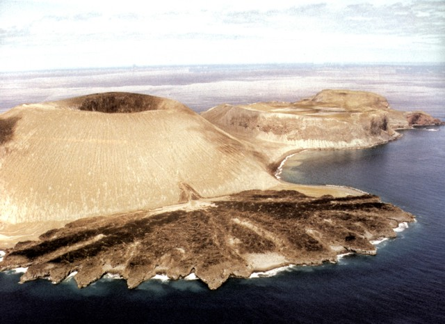 "San Benedicto - in the foreground, the Barcena and its lava delta, in the center of the island, with its ""flat"" summit, the crater Herrera - photo Barcena - washing delta on SE flank - Photo by Hugo Delgado Granados, 1993 (Universidad Nacional Autónoma de México)"