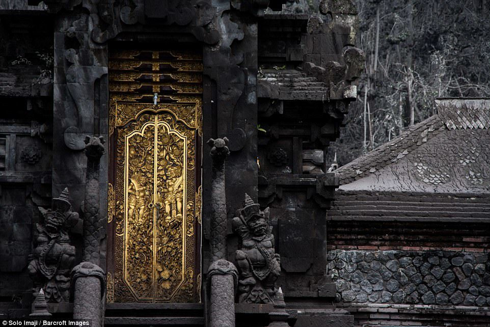 Life in the ashes of the forbidden zone - the golden portal of the temple contrasts with the walls blackened by the ashes of the Agung - photo Solo Imaji - Barcroft Images
