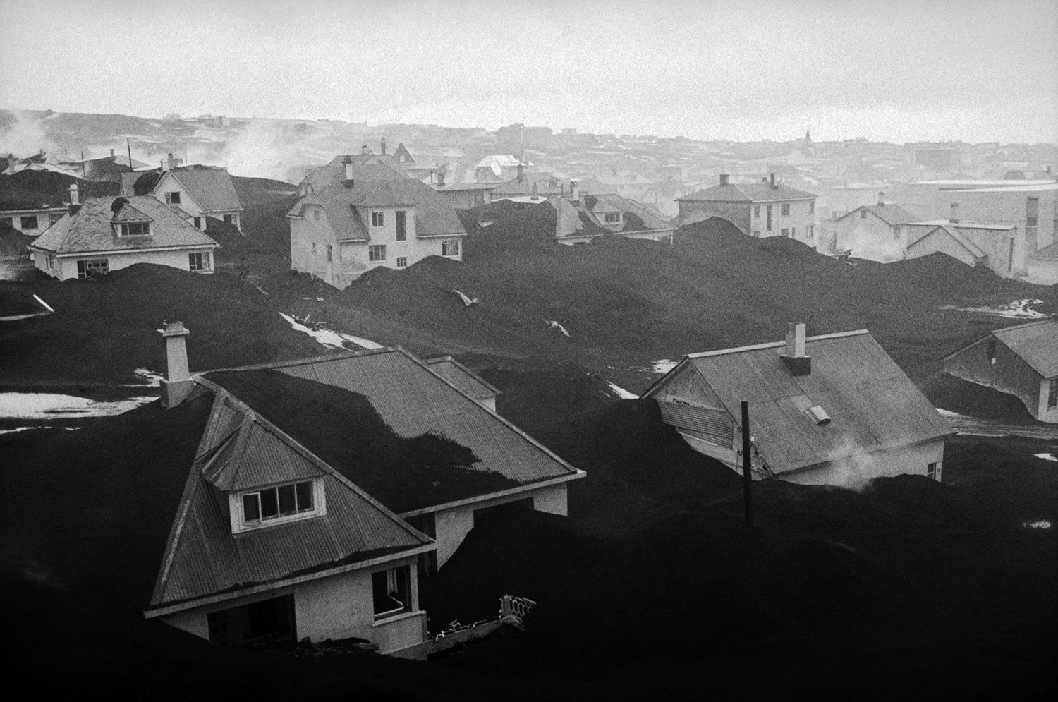The houses of Vestmannaeyjar, buried under the ashes, after the eruption of 1973 - photo Owen Franken / Corbis in The Atlantic