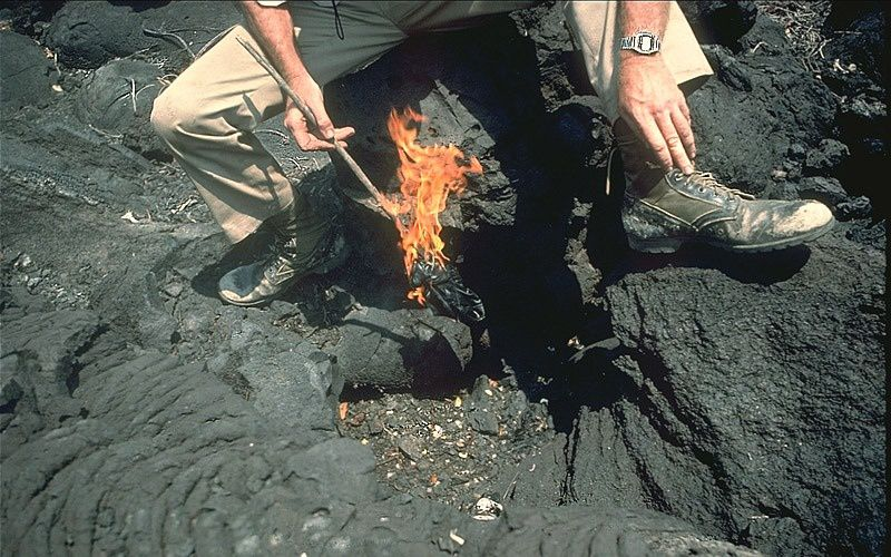 Dry carbon dioxide fumigates on a Nyamuragira lava flow of 1938 - the flame burns in the air, but goes out when lowered into a CO2-filled depression - photo by M.Tuttle 02.1989 / USGS