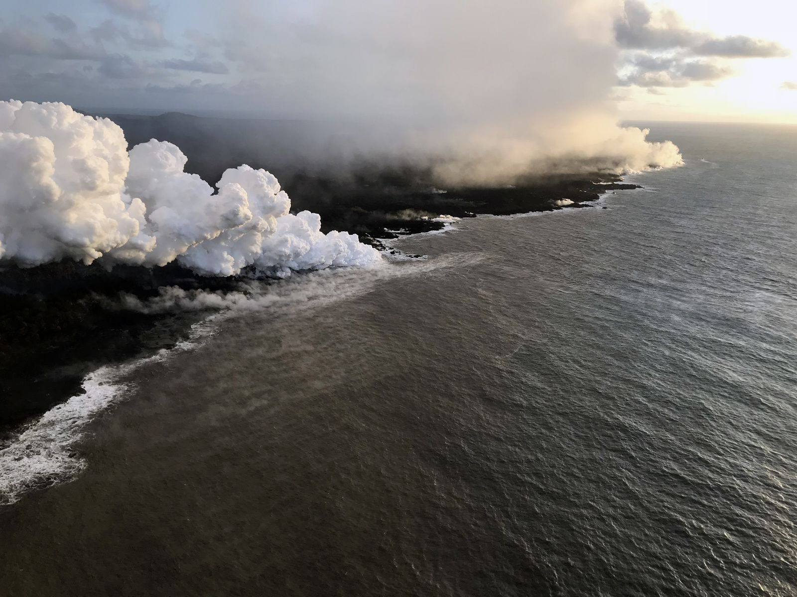 Kilauea East Rift Zone - The entrance to the lava at sea at Ahalanui Park is marked by a large plume of laze (in the center-left) while the fumes are more diffuse on the rest of the ocean front. - photo 12.07.2018 / USGS