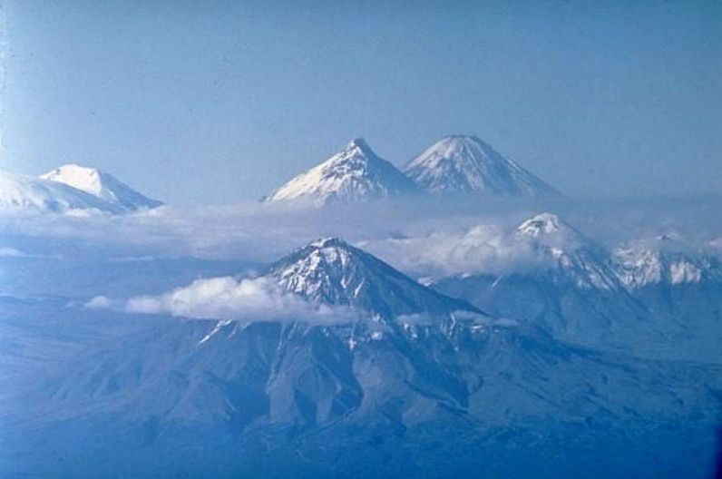 This dramatic photo looks north along the cluster of large stratovolcanoes forming the Kliuchevskaya volcano group. Udina volcano (foreground) and the twin Zimina volcano (middle right) are Holocene centers without historical eruptions. Kamen volcano (top center) and Kliuchevskoi (top right) are Kamchatka's two highest peaks. Ushkovsky volcano (top left) lies at the NW end of the volcano group and has had a single historical eruption. Bezymianny volcano is hidden by clouds below Kamen. Photo by Oleg Volynets (Institute of Volcanology, Petropavlovsk) via GVP