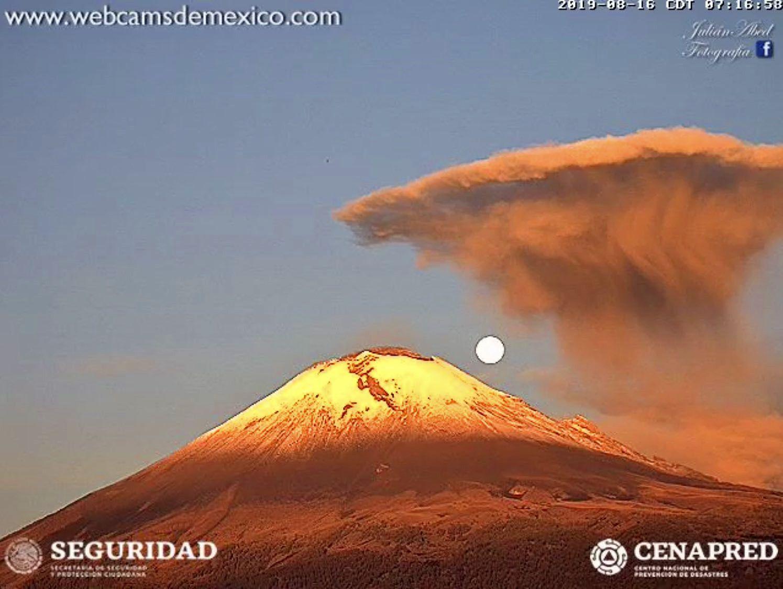Popocatépetl 16.08.2019 / 7h16 - malgré le danger, le volcan peut présenter des images poétiques au lever du jour, avec la Lune et les cendres exhalées quelques instants avant - webcamsdeMexicoWdM
