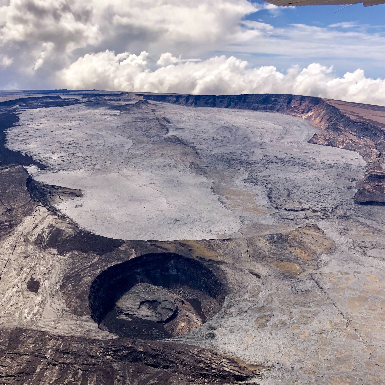 Mauna Loa - Summit caldera, Moku'āweoweo, intersected by a crack formed by the eruption of 1984, and the pit crater Lua Poholo, bottom left - Civil Air Patrol photo of October 20, 2019