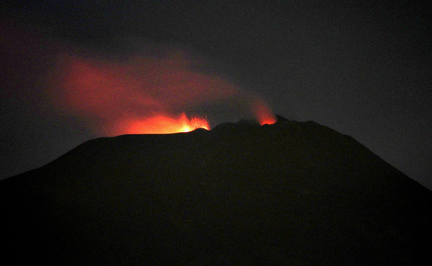 "L 'Etna seen from tremestieri Etnéo in the evening of March 17, 2020. We see strombolian activities with two mouths inside the crater of Voragine, where the central cone was born a little more than 6 months ago. On the right, we see a modest glow at the ""saddle cone"" of the new crater in the Southeast, where Strombolian explosions and low ash emissions are observed. - photo Boris Behncke / INGVvulcani"