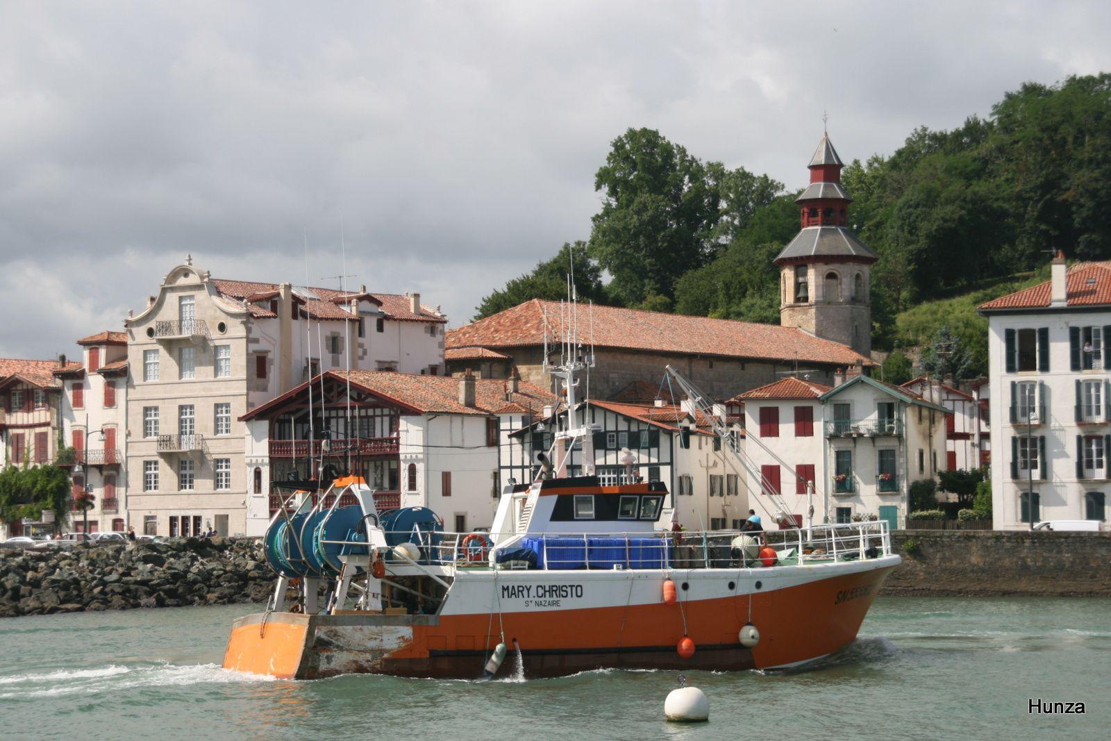 Un bateau sort du port de Saint-Jean de Luz avec, en arrière plan, l'église de Ciboure