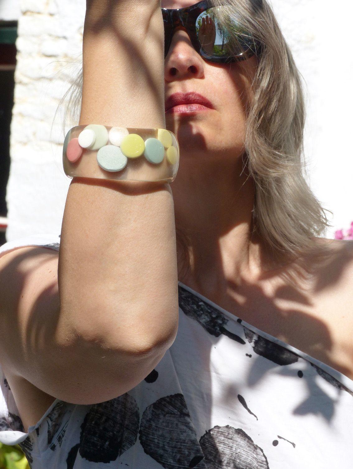 Kunstharz Armreif, transparent mit eingebetteten Punkten.