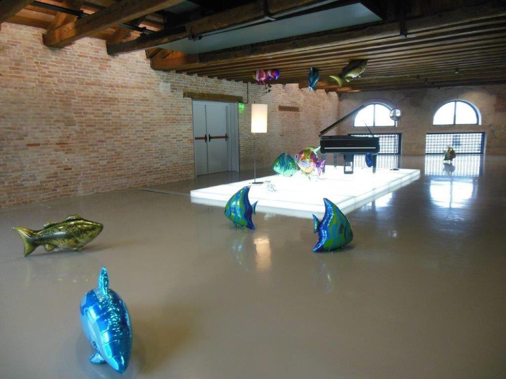 """Le titre de l'oeuvre de Philippe Parreno, """"Quasi Objects : My Room is a Fish Bowl, AC/DC Snakes, Happy Ending, Il Tempo del Postino, Opalescent acrylic glass podium, Disklavier Piano"""" (2014) en dit long sur la mise en scène élaborée qu'il a conçue. Une oeuvre qu'on traverse sous la musique de Franz Liszt et la luminescence du podium."""