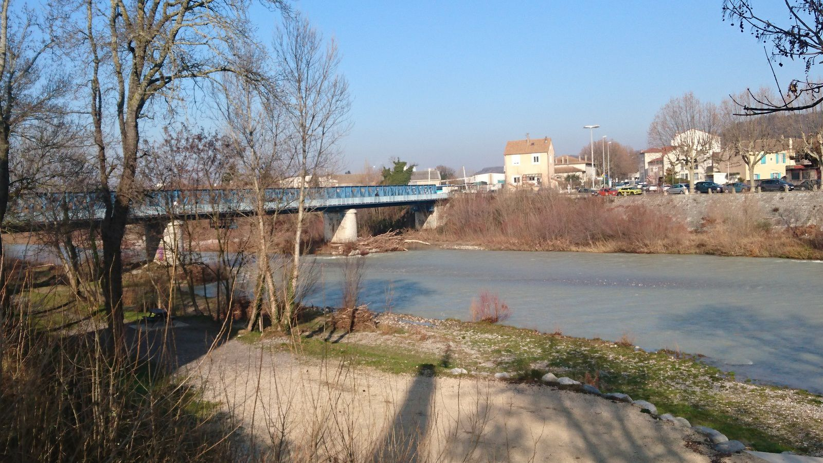 """Le pont de chemin de fer, dit """"pont bleu"""". Une passerelle piétonnière le longe."""
