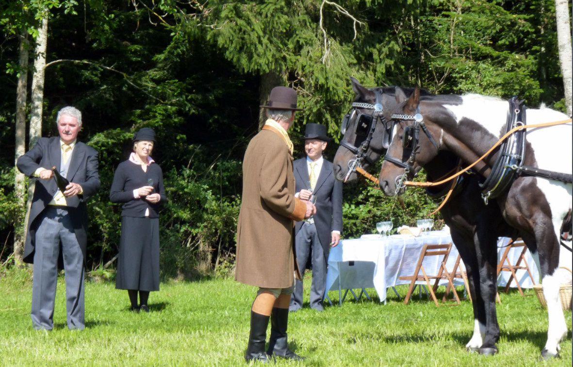 Monsieur Macrez sabrant le champagne sous l'œil interrogatif  de ses chevaux et de ses invités