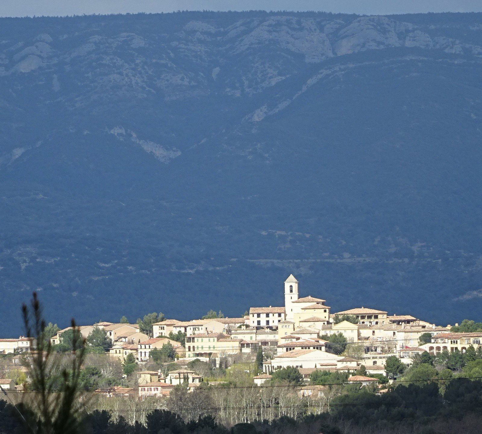 Le village accroché à la colline est nimbé de soleil.