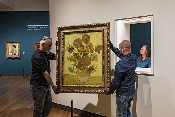 Creditline: Art handlers are hanging Sunflowers in such a way that for the first time in history the back of the painting will also be on view.