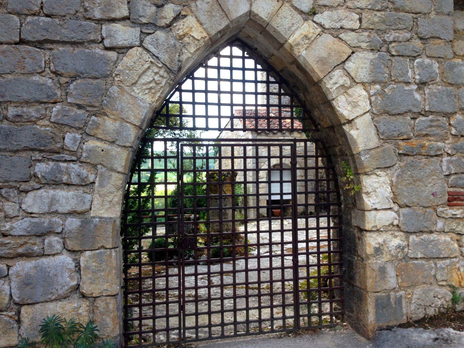 Aperçu du jardin de l'extérieur du musée par une porte ogivale.