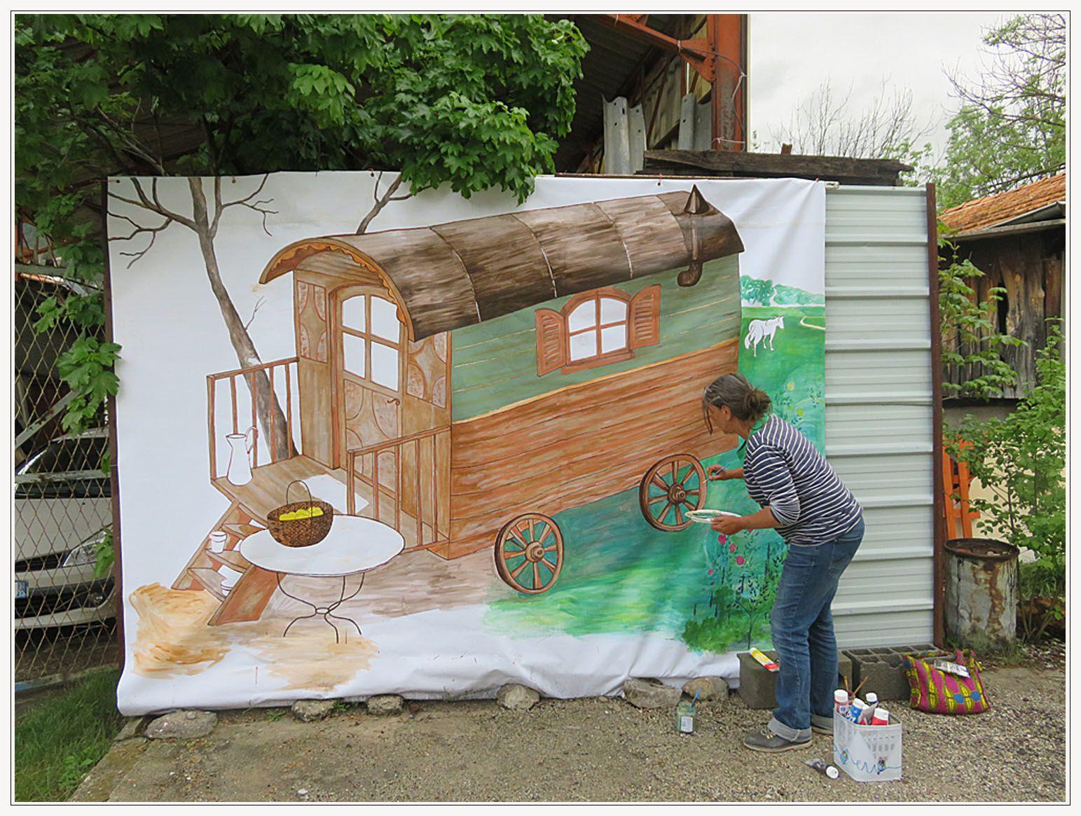 Devant la boutique La Verdine, la roulotte appelée verdine, tout un symbole et une toile d'envergure par Nathalie Martel, artiste plasticienne originaire d'Allons