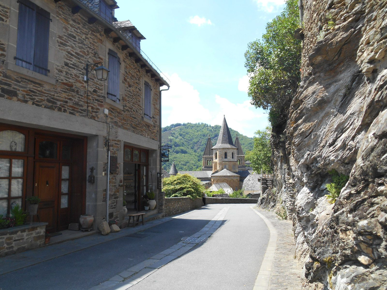 Entrée du village et première vue sur l'église abbatiale Sainte-Foy.