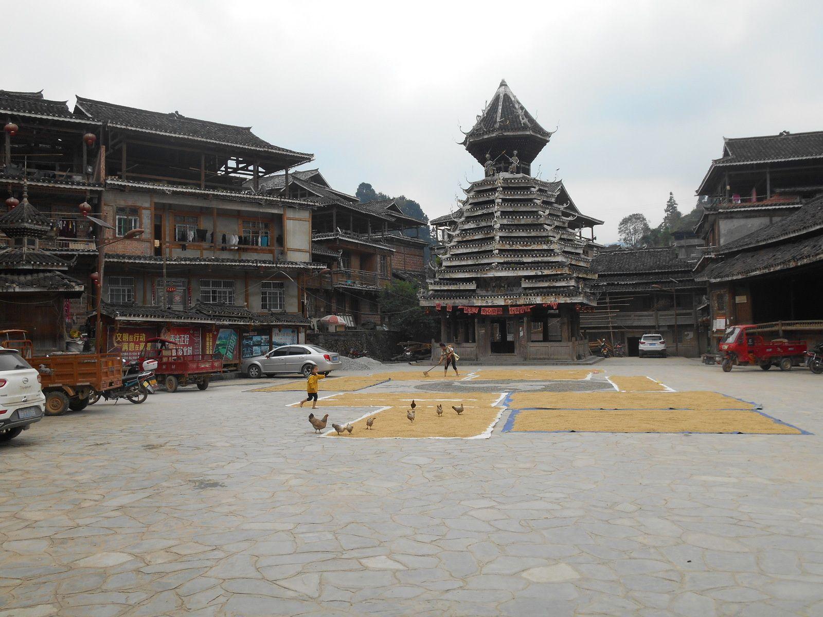 La place centrale sert de lieu de séchage du riz...Les enfants chassent les poules.