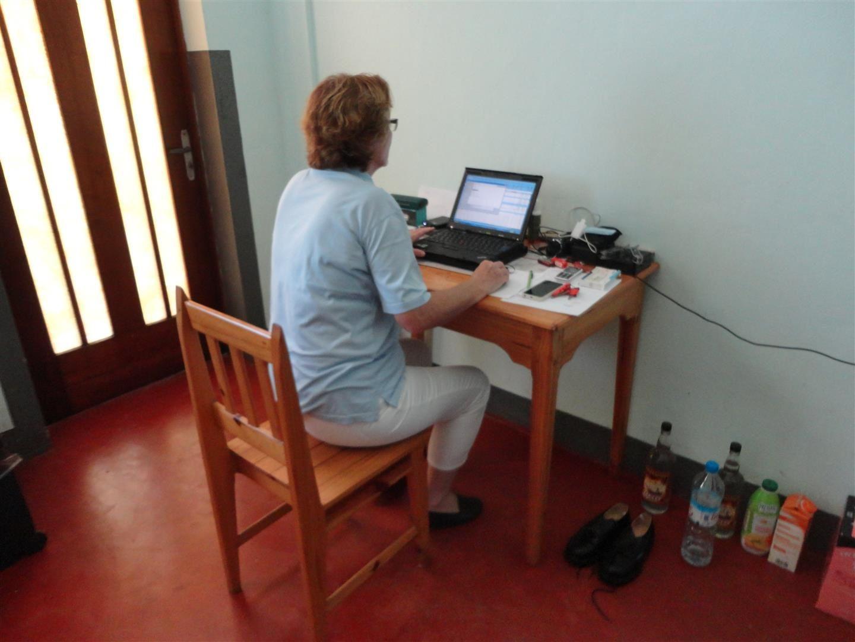 Maggy, le matin dans sa chambre de la résidence de l'évêché, rédige au jour le jour le compte rendu des activités de la mission électricité avant de partir sur le chantier.