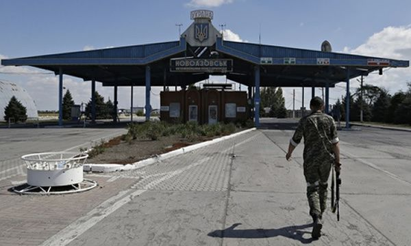 A Pro-Russia rebel walks at the Novoazovsk border crossing point, in eastern Ukraine