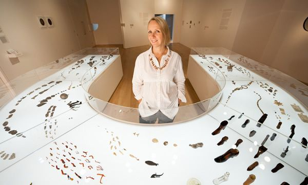 Felicity Powell with her display for Charmed Life: The Solace of Objects at the Wellcome Collection, central London, 2011. She designed and built the horseshoe-shaped illuminated vitrine to display a shoal of lucky charms