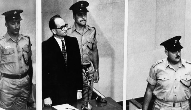 Adolf Eichmann standing in his glass cage, flanked by guards, in the Jerusalem courtroom where he was tried in 1961 for war crimes committed during World War II.
