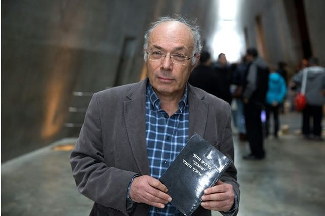 """Israeli Dan Michman, head of the Yad Vashem International Institute for Holocaust Research, holds a copy of the Hebrew version of """"Mein Kampf"""" book in Jerusalem, on December 31, 2015"""